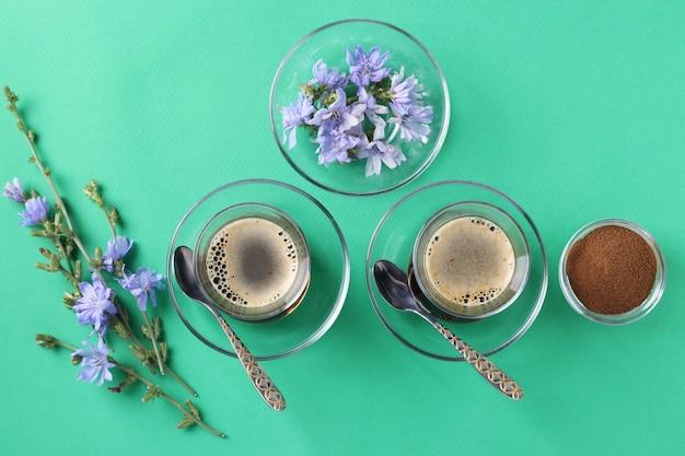 Boisson à la chicorée dans deux tasses en verre, avec concentré et fleurs sur vert