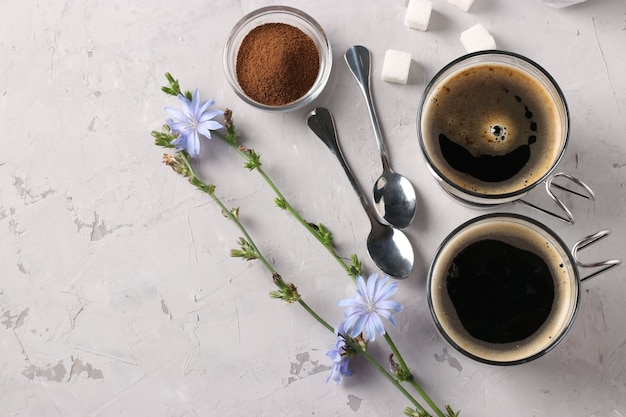 Boisson à la chicorée dans deux tasses en verre, avec du concentré et des fleurs sur fond gris. boisson à base de plantes saine, substitut de café, espace pour le texte, vue de dessus