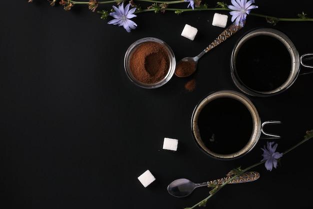 Boisson à la chicorée dans deux tasses en verre, avec du concentré et des fleurs sur une surface noire