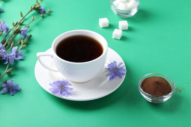 Boisson de chicorée en tasse blanche, avec concentré et fleurs sur table verte. boisson aux herbes saine, substitut de café, gros plan