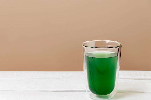 Boisson à la chlorophylle verte dans un verre sur une table blanche avec espace de copie