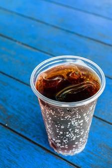 Boisson cola avec des glaçons sur planche de bois bleu