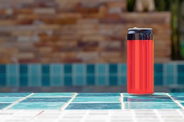 Une boisson en conserve rouge et noire sur le carrelage au bord de la piscine.