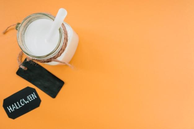 Boisson de couleur blanche en bouteille avec de la paille et une étiquette près de l'inscription halloween