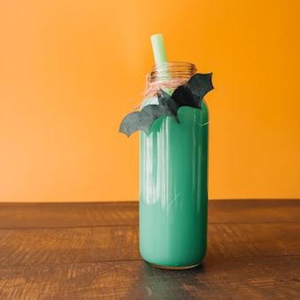 Boisson de couleur verte en bouteille avec batte faite main sur fond orange