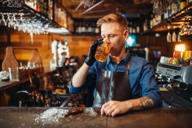 Boisson de dégustation de barman masculin au comptoir du bar