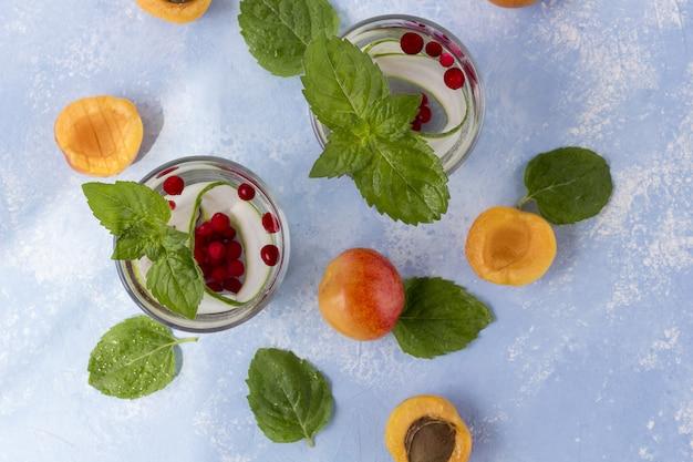 Boisson détox fraîche et fraîche avec du concombre, des baies et des pêches ou des aprikotes.