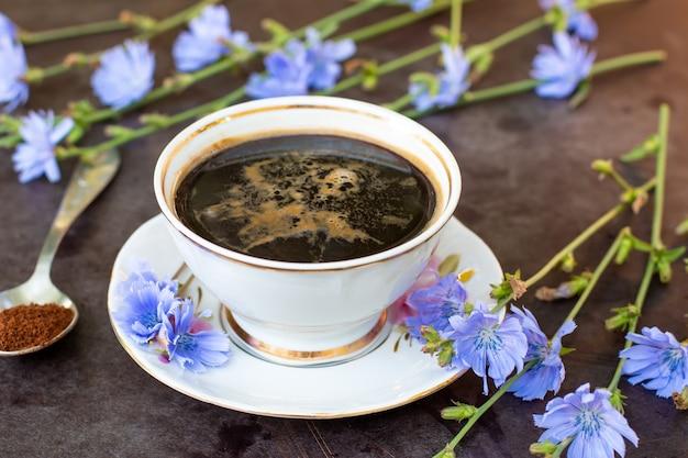 Boisson diététique chicorée dans une tasse - succédanés de café, poudre et feurs. boisson à base de plantes. mise au point sélective