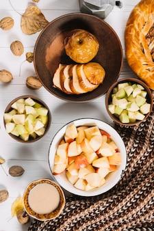 Boisson et écharpe près des pommes
