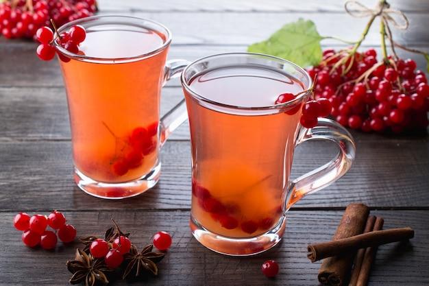 Boisson épicée chaude avec viburnum dans des tasses en verre avec des baies fraîches de viburnum sur une table de cuisine dsrk.