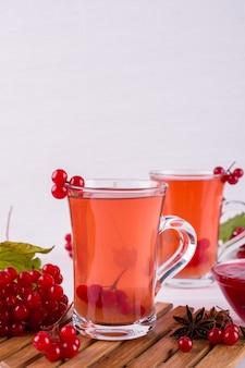 Boisson épicée chaude avec de la viorne dans des tasses en verre avec des baies fraîches de viorne sur une table de cuisine blanche.