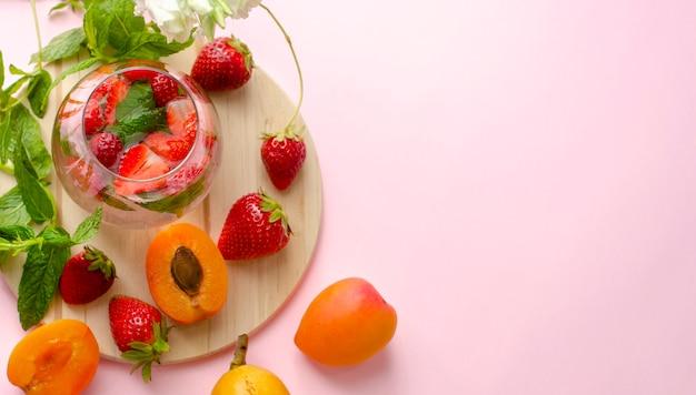 Boisson d'été aux fraises et à la menthe sur fond rose