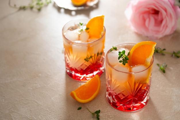 Boisson d'été avec des fraises, des oranges et des herbes fraîches, de délicieux verres de limonade faits maison avec du sirop