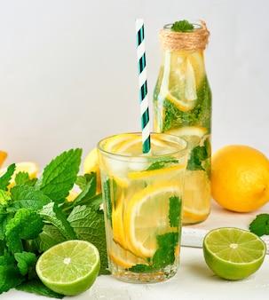 Boisson d'été limonade aux citrons, feuilles de menthe, citron vert dans une bouteille en verre