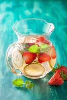 Boisson d'été rafraîchissante avec citron vert aux fraises et concombre en pot