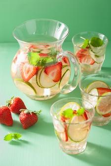 Boisson d'été rafraîchissante avec citron vert aux fraises en pot et verres