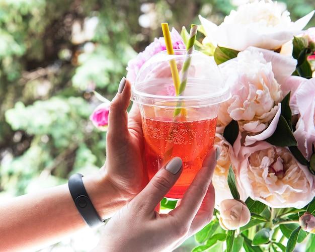 Boisson d'été rafraîchissante à la fraise dans les mains des femmes devant la fenêtre et un bouquet de pivoines