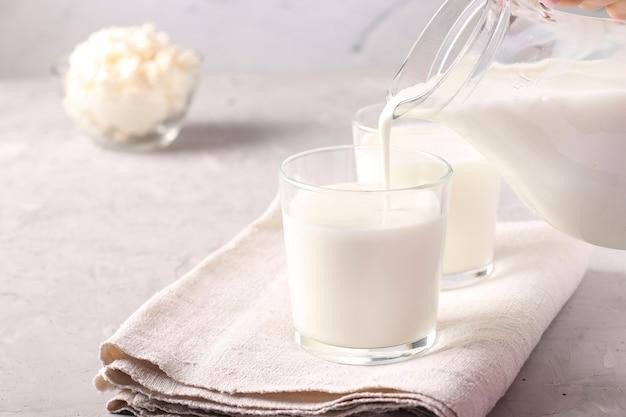 La boisson fermentée kéfir ou ayran est versée dans un verre à partir d'une cruche, ainsi que du fromage cottage dans un bol sur une surface gris clair, espace de copie, gros plan
