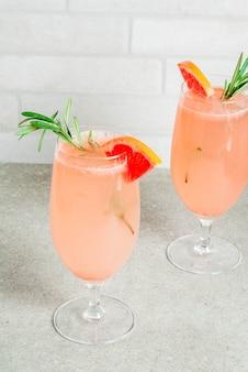 Boisson festive pour la fête de noël, cocktail mimosa au champagne, pamplemousse et romarin, sur conte de pierre,
