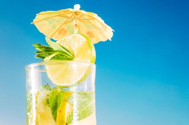 Boisson fraîche au citron vert et à la menthe tranchés dans un verre décoré de parapluie