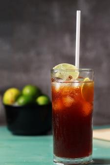 Boisson fraîche au thé glacé au citron et à la lime en été et par temps chaud, boisson fraîche glacée au thé noir et tranche de citron vert