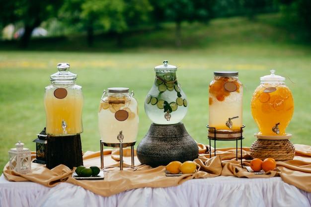 Boisson fraîche dans des pots de citrons, citron vert et oranges sur une table de fête blanche