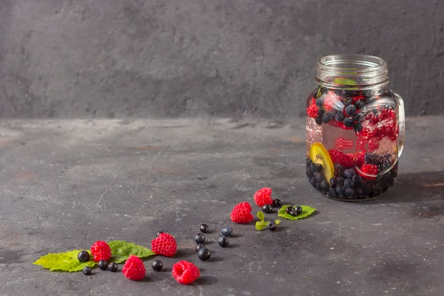 Boisson fraîche détox fraîche avec des framboises, des bleuets et des kiwis dans une tasse de pot mason. limonade dans un verre à la menthe. le concept d'une bonne nutrition et d'une alimentation saine. régime de fitness. espace copie pour tex