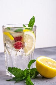 Boisson fraîche d'eau glacée avec citron, framboises et feuille de menthe