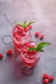 Boisson fraîche de jus de baies glacées à la menthe, limonade aux framboises d'été dans deux verres avec des pailles sur la table en béton en pierre, angle