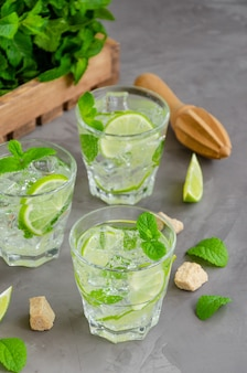 Boisson fraîche de mojito d'été avec tranches de citron vert, menthe, glaçons et cassonade dans un verre