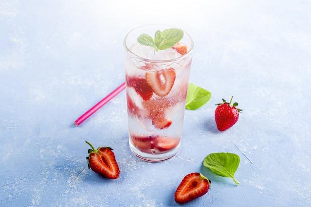 Boisson fraîche rafraîchissante avec fraise et menthe sur table bleue. limonade d'été ou thé glacé dans un verre. cocktail de mojito avec des glaçons.