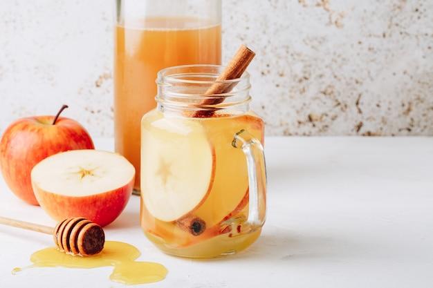Boisson fraîche et saine avec du vinaigre de cidre, du miel, des pommes et de la cannelle