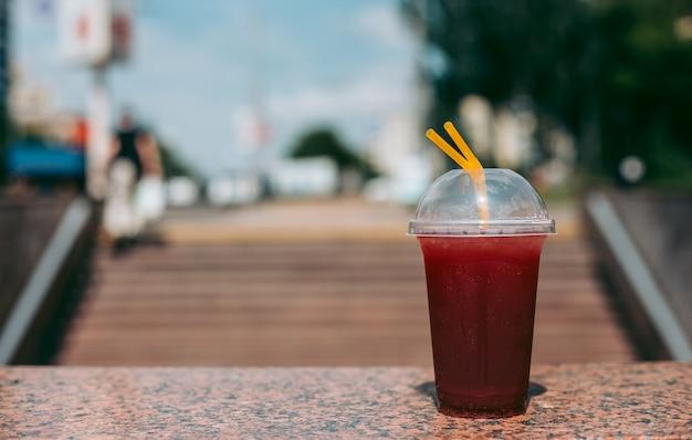 Boisson à la framboise rouge dans un verre en plastique avec une paille