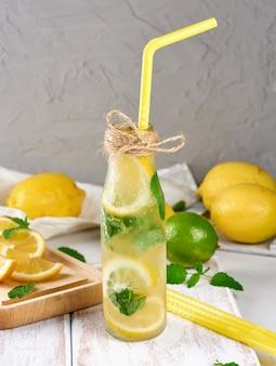 Boisson froide aux citrons, feuilles de menthe, citron vert dans une bouteille en verre