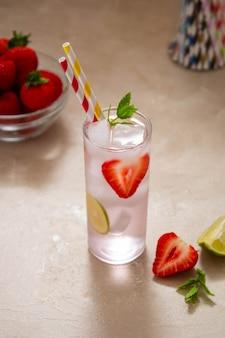Boisson froide aux fraises avec baies fraîches, citron vert et menthe. boisson froide d'été avec paille de papper