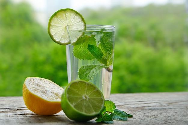 Une boisson froide à base de citron, de citron vert et de menthe dans une tasse en verre