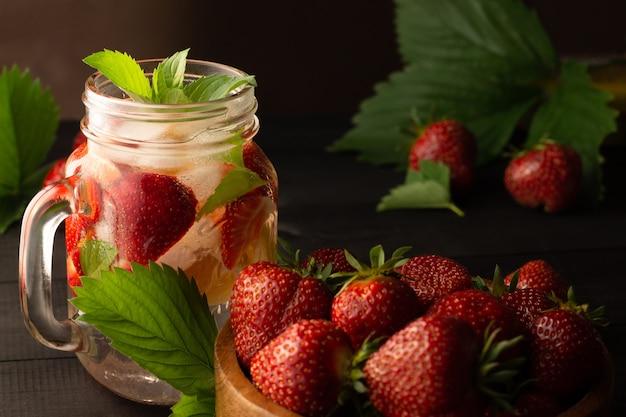 Boisson froide d'été à la menthe, glace, citron et fraises sur fond de bois sombre