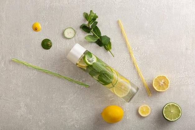 Boisson gazeuse dans une bouteille à la mode. à boire dans de l'eau claire avec du citron vert, du citron, de la menthe. sans sucre
