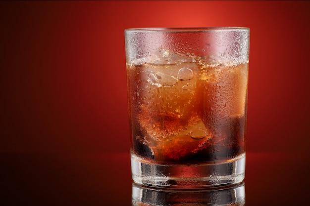 Boisson gazeuse avec de la glace dans un endroit en verre