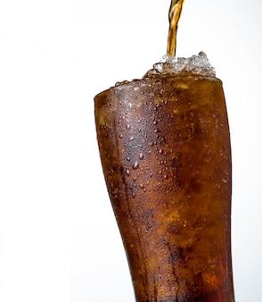 Boisson gazeuse avec des glaçons pilés en verre isolé sur fond sombre avec espace de copie. il y a une goutte d'eau sur la surface en verre transparente.