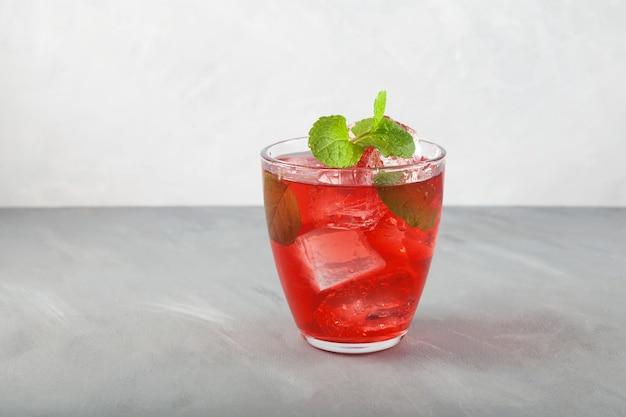 Boisson gazeuse rafraîchissante d'été rouge avec glace ou thé glacé aux fruits