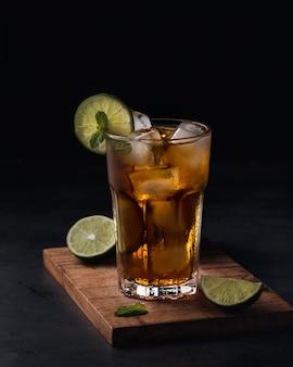 Boisson gazeuse rafraîchissante avec des tranches de citron vert dans une tasse en verre sur fond noir