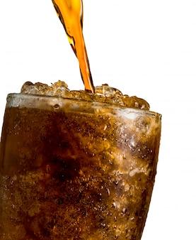 Boisson gazeuse versant au verre avec de la glace isolé sur fond blanc avec un tracé de détourage et copie espace il y a une goutte d'eau sur la surface en verre transparente.
