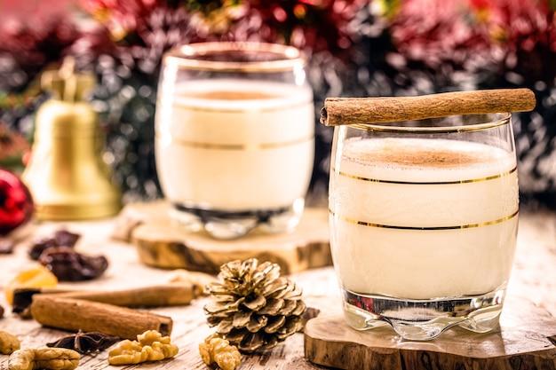 Boisson d'hiver à base d'œufs, de liqueur, de rhum et de cannelle, appelée lait de poule de noël, décorée de noix, de biscuits et de fruits secs