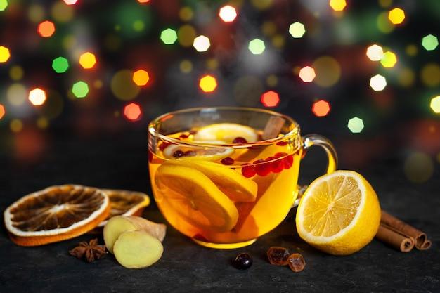 Boisson d'hiver parfumée chaude avec du citron, de la canneberge et du gingembre dans une grande tasse en verre sur une table sombre