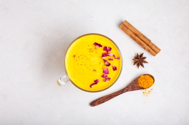 Boisson indienne golden milk ou latte au curcuma décorée de pétales de rose boisson asiatique tendance