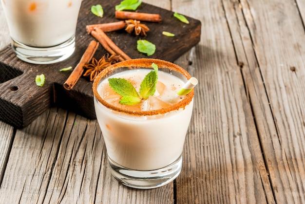 La boisson indienne traditionnelle est le thé glacé ou le chai masala, avec des glaçons de chai, de lait et de feuilles de menthe. avec des pailles rayées, sur une planche de bois. sur une vieille table en bois rustique. espace copie