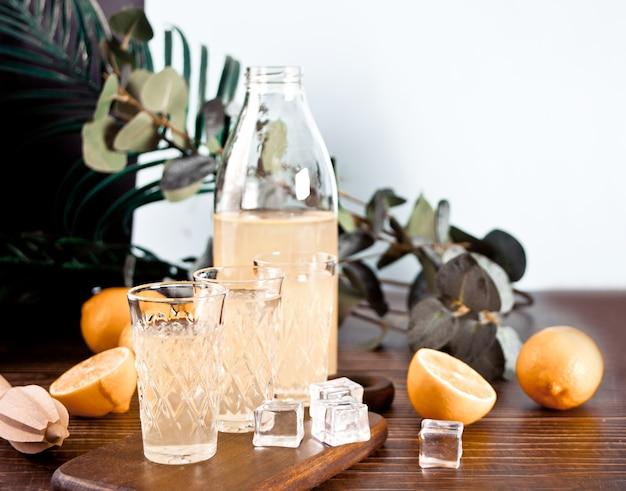 Boisson italienne liqueur de citron limoncello dans une bouteille et verres vides sur la table en bois.