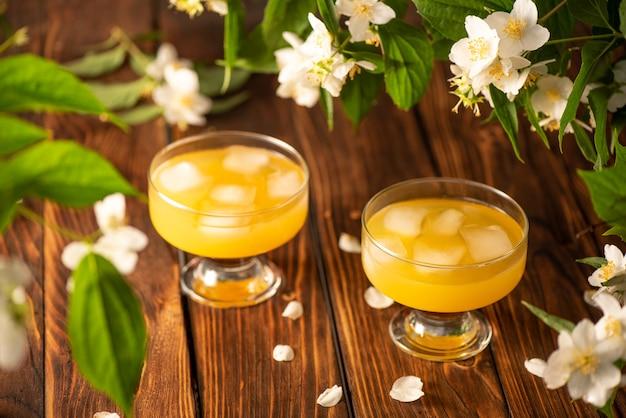 Boisson jaune avec de la glace sur une table en boismise au point sélective