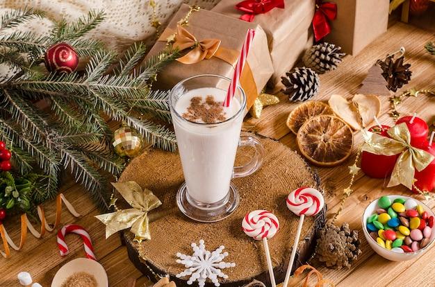 Boisson de lait de poule de noël et du nouvel an dans une tasse en verre sur un support en bois sur la table avec des cadeaux, des biscuits de noël, des bougies, des bonbons et des branches d'arbres de noël. pour les recettes de boissons de vacances.